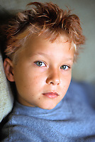 Close up portrait of a 10 year old boy with orange hair gel