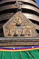 Kathmandu, Nepal.  Images Depicting the Buddha.  Behind can be seen the first four of 13 tapering circular stages resting above the harmika (square base) of the Swayambhunath stupa, representing the 13 stages of perfection on the way to nirvana.