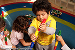 Preschool Headstart 3-5 year olds boy playing with construction toy filling together colorful plastic tubes horizontal