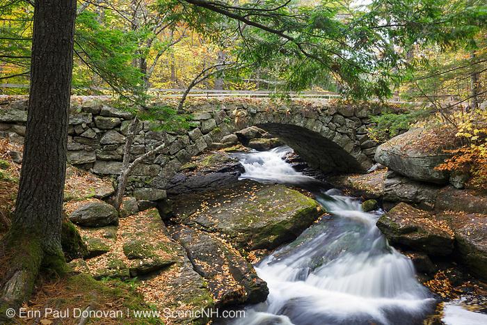 Gleason Falls Bridge in Hillsborough, New Hampshire during the autumn months. This stone bridge spans Beard Brook.