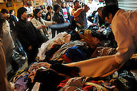 Women buy clothes from a street seller in Hong Kong's Central District. Hong Kong's slumping economy will shrink further in the first half of 2009..