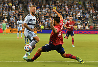 KANSAS CITY, KS - JULY 31: Johnny Russell #7 of Sporting Kansas City passes the ball past Ryan Hollingshead #12 of FC Dallas during a game between FC Dallas and Sporting Kansas City at Children's Mercy Park on July 31, 2021 in Kansas City, Kansas.
