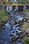 Water spilling over a small dam into a rocky stream. NH