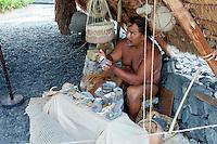Native Hawaiian man holding artifacts while giving Hawaiian cultural lecture in Pu'uhonua o Honaunau National Historical Park, Big Island.