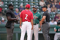 Home plate umpire James Jean, left, talks with Greenville Drive manager Iggy Suarez and Greensboro Grasshoppers manager Kieran Mattison and field umpire Ray Valero before a game on Friday, July 23, 2021, at Fluor Field at the West End in Greenville, South Carolina. (Tom Priddy/Four Seam Images)