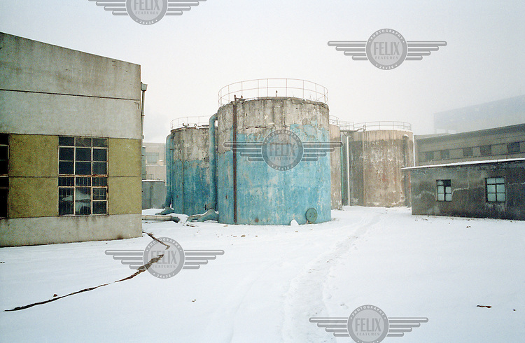 Old storage tanks at a coal-fired power station. China is in the process of building over 500 new coal power plants to meet the increasing energy demand.