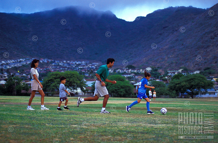 Family playing soccer in an open field in Hawaii Kai, Oahu