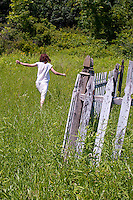 Young woman walking through tall grass past wooden picket fence