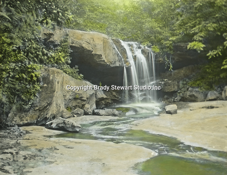 Fayette County PA: Waterfall on one of Bear Run's streams.  The Stewart family often took weekend trips to Fayette County's Bear Run.  Bear Run is a nature reserve today and is near Frank Lloyd Wright's Fallingwater. The Stewart's visited Alice Brady Stewart's sister and brother who lived in Stewart Township PA. To give family and friends a better feel for the adventure, he hand-color black and white negatives into full-color 3x4 lantern slides.  The Process:  He contacted a negative with another negative to create a positive slide.  He then selected a fine brush and colors and meticulously created full color slides.  Keep in mind, this black and white image was taken in 1905.