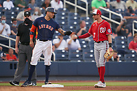Houston Astros Carlos Correa (1) fist bumps Trea Turner (7) during a Major League Spring Training game against the Washington Nationals on March 19, 2021 at The Ballpark of the Palm Beaches in Palm Beach, Florida.  (Mike Janes/Four Seam Images)