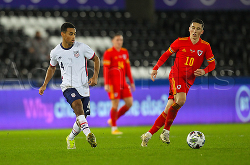 12th November 2020; Liberty Stadium, Swansea, Glamorgan, Wales; International Football Friendly; Wales versus United States of America; Tyler Adams of USA passes the ball while under pressure from Harry Wilson of Wales