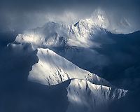 Alaska's Chugach Range photographed from above as clouds sweep over the snow covered peaks.