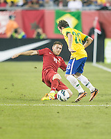 Portugal defender Antunes (19) slides to tackle Brazil midfielder Bernard (20).  In an International friendly match Brazil defeated Portugal, 3-1, at Gillette Stadium on Sep 10, 2013.
