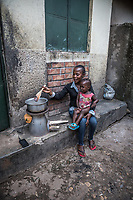 Uganda, Hoima. Hope Lydia Businge, 26 years, has a two year old daughter and runs a hair salon. At home she uses a BioLite cook stove that charges a light and mobile phone. With her daughter.
