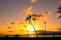 A radiant orange sun sets behind swaying palm trees and western Oahu mountains as seen from Ala Moana Beach Park on Oahu.