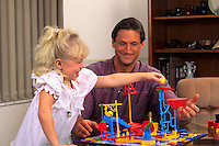 Father and daughter having fun and spening time together playing board game at home