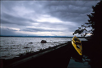 Dramatic storm clouds over Hudson River and a yellow kayak.