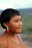 Roraima, Brazil. Young Yanomami woman with red and white bead ear decorations.