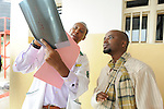 The medical director of Kinigi District Hospital, Rwanda, inspects a broken arm of a patient who was injured in a machete attack by an unknown assailant.