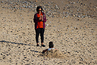 WEATHER PICTURE WALES<br /> A lady takes a photo of a young girl in the sand during the unusually warm weather in Langland Bay near Swansea, Wales, UK. Wednesday 27 February 2019