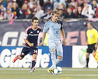 Sporting Kansas City defender Chance Myers (7) passes the ball as New England Revolution midfielder Diego Fagundez (14) closes. In the first game of two-game aggregate total goals Major League Soccer (MLS) Eastern Conference Semifinal series, New England Revolution (dark blue) vs Sporting Kansas City (light blue), 2-1, at Gillette Stadium on November 2, 2013.