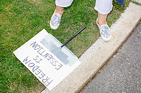 """A sign reading """"Freedom is essention"""" lays on the ground as people gather for an anti-lockdown protest organized by the alt-right group Super Happy Fun America near the home of Massachusetts governor Charlie Baker in Swampscott, Massachusetts, on Sat., May 16, 2020. The protest was in defiance of Massachusetts orders mandating face coverings and social distancing and prohibiting gatherings larger than 10 people during the ongoing Coronavirus (COVID-19) global pandemic. The state's stay-at-home order is expected to be updated on May 18, 2020, with a phased reopening plan issued by the governor as COVID-19 cases continue to decrease. Anti-lockdown protests such as this have become a conservative cause and have been celebrated by US president Donald Trump. Many of the protestors displayed pro-Trump messages or wore Trump campaign hats and shirts with phrases including """"Trump 2020"""" and """"Keep America Great."""" Super Happy Fun America, organizers of the protest, are an alt-right organization best known for creating the 2019 Boston Straight Pride Parade."""