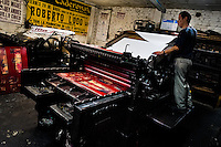 A Colombian master printer works on the ancient letterpress machine in the print shop in Cali, Colombia, 1 June 2012. Letterpress printing, invented by Johannes Gutenberg in the 15th century, remained the primary way to print and distribute information until the second half of the 20th century. The process of letterpress printing consists of composing movable types into the bed of a press, inking it, and pressing paper against it to create an impression. Nowadays, due to the offset printing expansion, there are few commercial print shops in the world keeping this traditional craftsmanship alive.