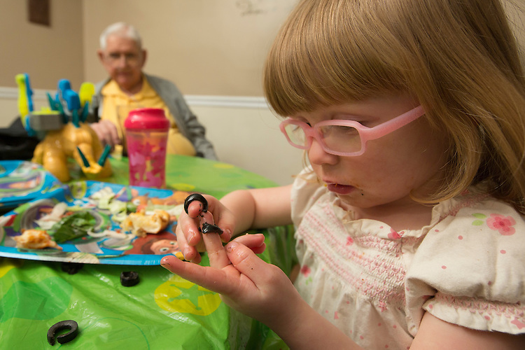 During a party for her third birthday, Marianne places black olives on her fingers while her great-grandfather, James Case, watches from a distance.