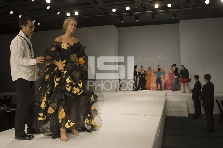 USWNT midfielder Leslie Osborne is shown how to walk down the runway before a fashion show held by South Korean fashion designer Andre Kim.  The show featured women from seven of the eight teams participating in the Queen Peace Cup in Seoul, South Korea.