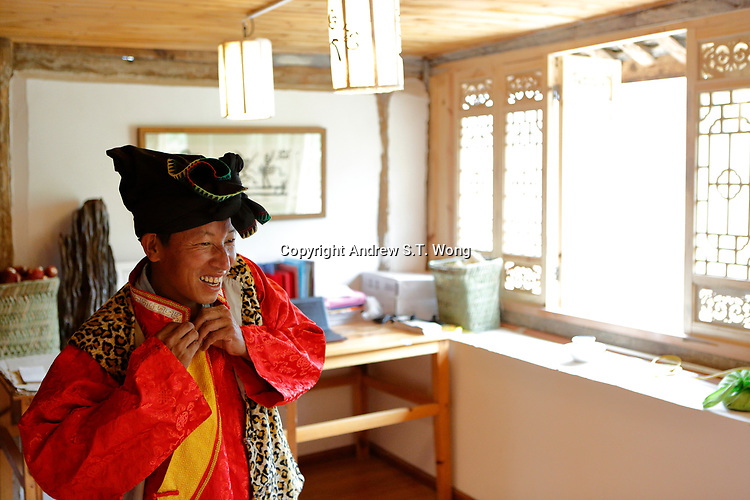 Wumu Village, Yulong County, Yunnan Province, China - Dongba priest He Jixian of the Naxi ethnic group puts on his traditional priest costumes, June 2019.