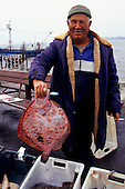 Nesebur, Bulgaria. Fisherman holding a red flat fish.