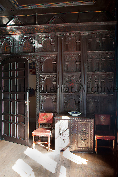 Ornately carved arches with inlaid decoration in a contrasting coloured wood clad the dining room walls