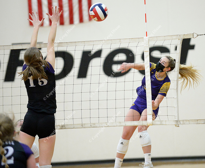 DeForest's Natalie Compe hits past Waunakee's Claire Holden, as DeForest tops Waunakee 3 sets to 1 in Wisconsin WIAA girls high school volleyball regional finals on Saturday, Apr. 10, 2021 at DeForest High School