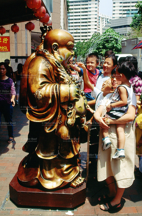Singapore. Downtown. Town center. Chinese family pays its respect to a golden figure of Buddha which stands at the entrance of a shopping center. © 2001 Didier Ruef