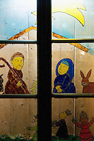 """Switzerland. Canton Tessin. Vira Gambarogno. The old town shows an exhibit of various Nativity scenes, illuminated at night for the Christmas holiday season. A Nativity Scene, may be used to describe any depiction of the Nativity of Jesus in art, but in the sense covered here, also called a crib or in North America and France a crèche (meaning """"crib"""" or """"manger"""" in French). It means a three-dimensional folk art depiction of the birth or birthplace of Jesus, either sculpted or using two-dimensional (cut-out) figures arranged in a three-dimensional setting. Christian nativity scenes, in two dimensions (drawings, paintings, icons, etc.) or three (sculpture or other three-dimensional crafts), usually show Jesus in a manger, Joseph and Mary in a barn (or cave) intended to accommodate farm animals. The scene includes the Magi or Three Wise Men and the Star of Bethlehem. Wood painting behind a glass window. © 2007 Didier Ruef"""