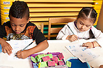 Education Preschool 3-4 year olds boy and girl sitting side by side doing writing/literacy activity using pencils and stamps, using opposite hands