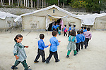 Karimabad, Pakistan.  Sept 24, 2010.  Young students file into their classroom at a tent school in Karimabad, built by the CAI for refugees whose villages where buried under the waters of the rising Hunza River, which rose to 200 feet at places, and still remains.  Photo by Ellen Jaskol.
