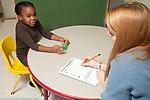 Education preschool 3-4 year olds female teacher administering development assesment psychological test to preschool student