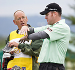 Tim Herron's caddier (left) and Troy Matteson (right) communicate before the 9th tee during the Turning Stone Resort Championship at Atunyote Golf Course in Verona, NY.