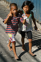 With a campaign calendar in hand, this young pair follows the motorcade of presidential candidate Fernando Poe Jr. as it wends through the narrow streets of Mariveles, Bataan Friday. 13 February 2004