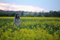 WEATHER PICTURE ENGLAND<br /> A lone woman walks at the end of dry but cold day, through a rape seed field near Sheffield in England, UK. Monday 17 April 2017