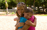 Mother and daughter hugging with love in park outdoors