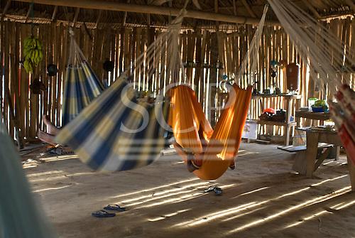 Xingu Indigenous Park, Mato Grosso State, Brazil. Aldeia Tuba Tuba (Yudja). Hammocks in the evening; ISA house.