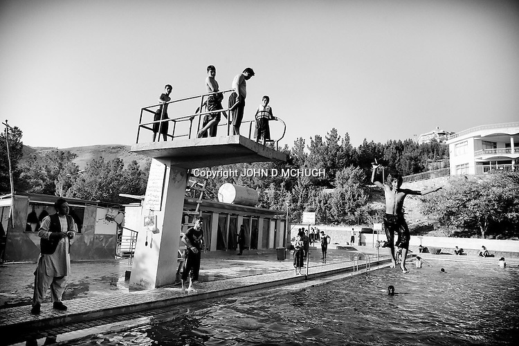 Young Afghans enjoy swimming and diving at a pool in Herat 20 September 2013. (John D McHugh)