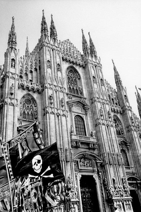 Italy. Lombardy Region. Milan. Pirate flag in front of Milan Cathedral (Italian: Duomo di Milano). The cathedral is the largest church in Italy and is dedicated to the Nativity of St Mary (Santa Maria Nascente). Jolly Roger (the skull and crossbones on a black flag) is the flag flown to identify a pirate ship about to attack during the early 18th century. © 1989 Didier Ruef