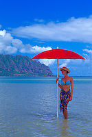 A woman stands under a red beach umbrella on a sand bar on windward Oahu with beautiful clear blue water and the Koolau mountains in the background.