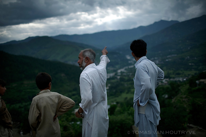 Pashtun men look toward the Swat river valley, where sever flooding took place, from the village of Barhampati in the Swat valley, Pakistan, on Aug. 25, 2010.