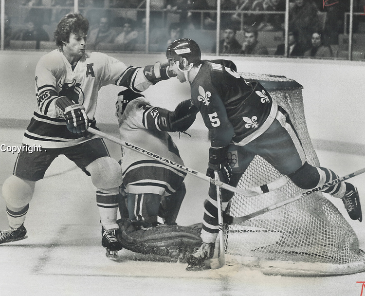 Out Of Harm's Way - Toros defenceman Jim Dorey (left) has decided Quebec Nordiques Rejean Houle can do little damage from the side of the net, so he was intent on keeping him there during action at Maple Leaf Gardens last night. With Houle safely out of the way, Toro goalie Dave Tataryn can concentrate on making the save, one of 42 shots Quebec took on goal. Toros won game by 7-4 score, though.<br /> <br /> 1975<br /> <br /> PHOTO :  Frank Lennon - Toronto Star Archives - AQP