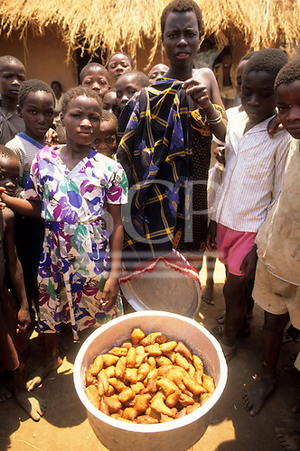 Kalepo, Tanzania. Village group with deep-fried sweet sort of doughnuts outside a thatched house.