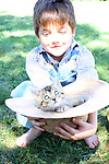 A young farmer boy holding a kitten in a straw hat